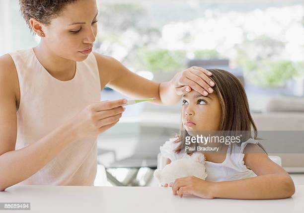 mother taking daughters temperature - fever stock pictures, royalty-free photos & images