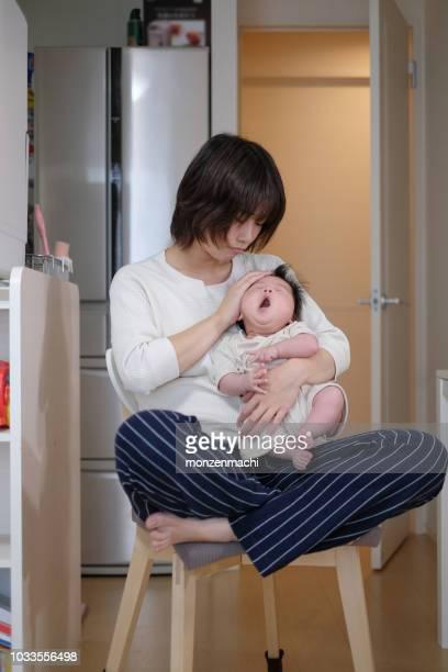 母は彼女の赤ちゃんの温度を取って