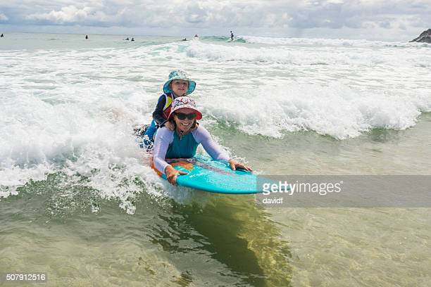 Mother Taking Her Young Child Surfing at the Beach