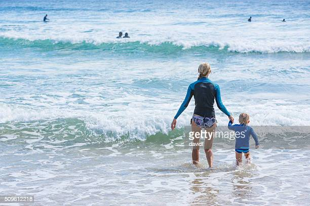 Mother Taking Her Young Child Swimming at the Beach