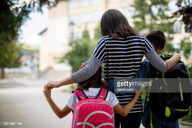 mother taking kids to school - family with two children stock photos and pictures