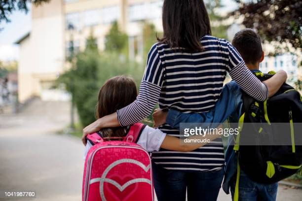 mother taking kids to school - riapertura delle scuole foto e immagini stock