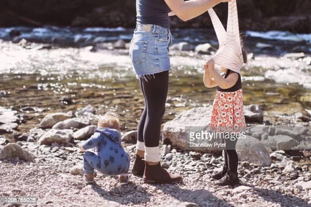 mother taking off sweatshirt of her daughter near a mountain stream - strip - fotografias e filmes do acervo