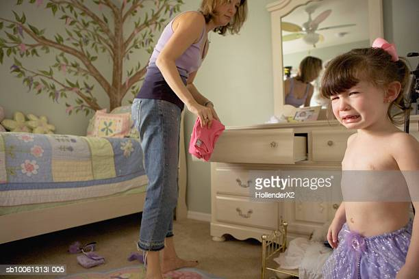 Mother taking out clothes from dresser, daughter (2-3) crying