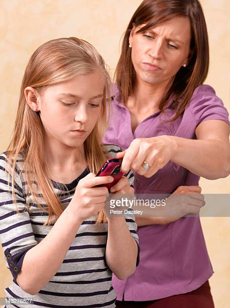 mother taking phone away from 10 year old girl - sad 10 year girl stock photos and pictures