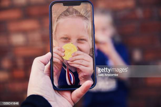 mother taking photo of child celebrating after winning at football - digital native stock pictures, royalty-free photos & images