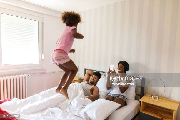 Mother taking photo of daughter jumping on parents bed