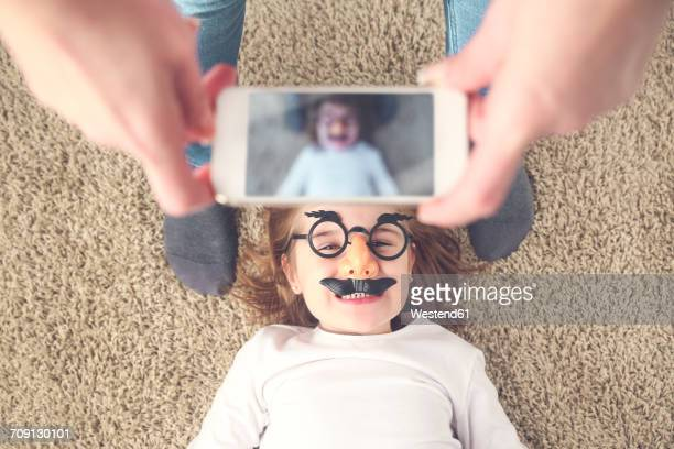 mother taking photo of her daughter with smartphone - childhood photos ストックフォトと画像