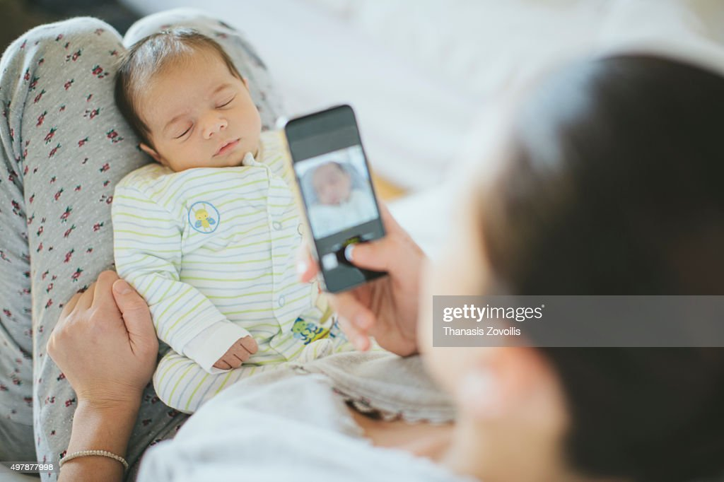 Mother taking photo of her newborn son : Stock Photo