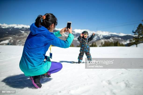 mother taking photo of her son snowboading. - vail colorado fotografías e imágenes de stock