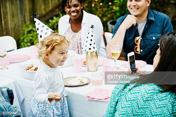 Mother taking photo of smiling toddler at party