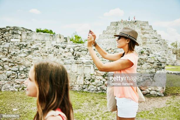Mother taking photo with smartphone while exploring Mayapan ruins with daughter