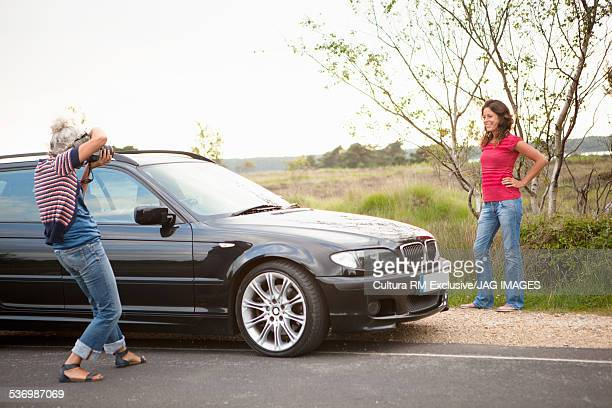 Mother taking photograph of daughter by car, Studland, Dorset