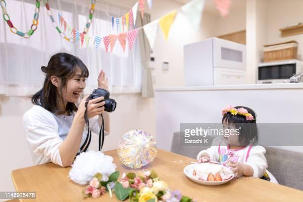 最初の誕生日に彼女の話さの写真を撮っている母 - 写真を撮る ストックフォトと画像