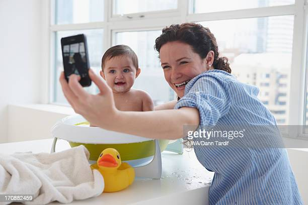 Mother taking picture with baby in bath