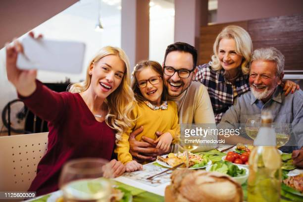 mother taking selfie of her multi-generation family at home - family at home stock photos and pictures