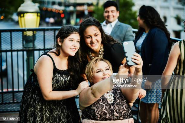 Mother taking selfie on smartphone with two daughters on restaurant deck
