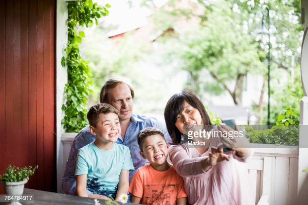 mother taking selfie with family in porch - asian twins stock photos and pictures