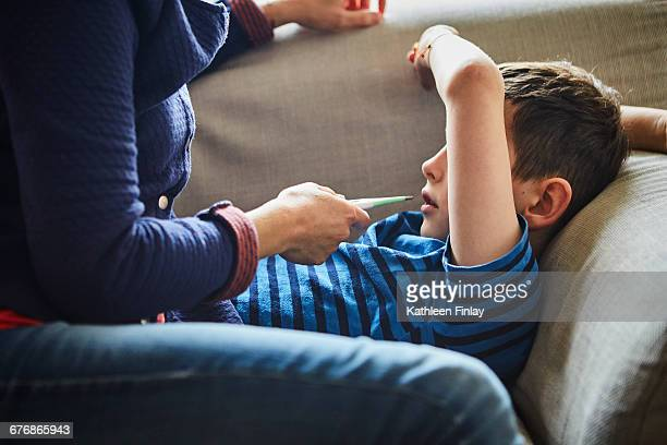 mother taking sons temperature with digital thermometer - digital thermometer ストックフォトと画像