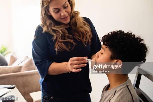 """madre tomando adolescente hijo temperatura en auto-aislamiento, covid-19. - """"martine doucet"""" or martinedoucet fotografías e imágenes de stock"""