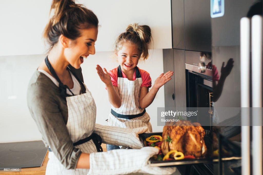 Mother taking the dinner out of the oven : Stock Photo
