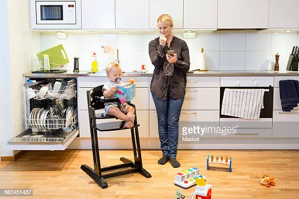 Mother talking on mobile phone in kitchen while baby boy sitting on high chair