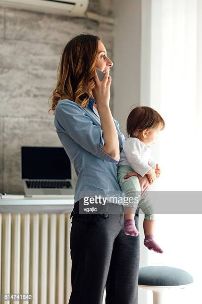 Mother Talking On The Phone And Holding Her Baby
