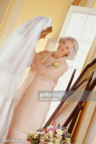 Mother talking to bride indoors