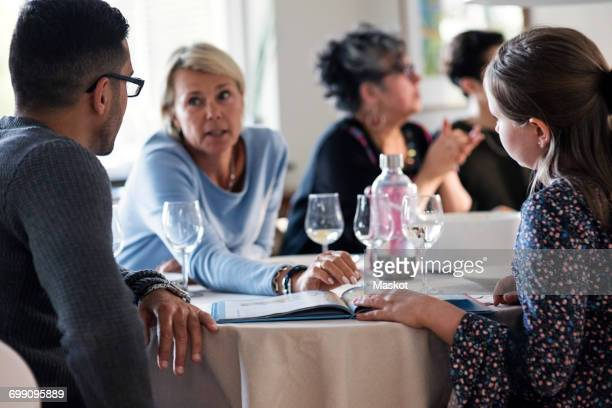 Mother talking to daughter and man with magazine at dinner party