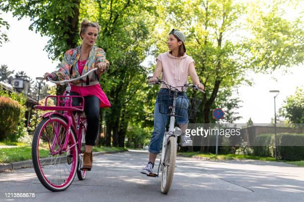 mamma pratar med dotter medan ridning cyklar - aunt bildbanksfoton och bilder