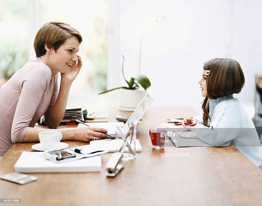 Mother Talking to Her Daughter Across a Table at Home : Stock Photo