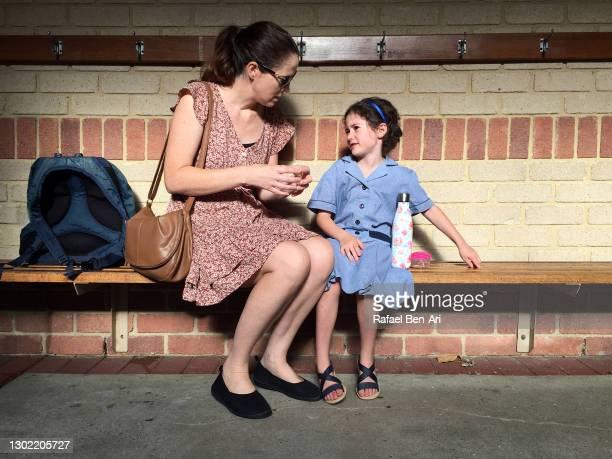 mother talking to her young daughter that is afraid to go to school - rafael ben ari imagens e fotografias de stock