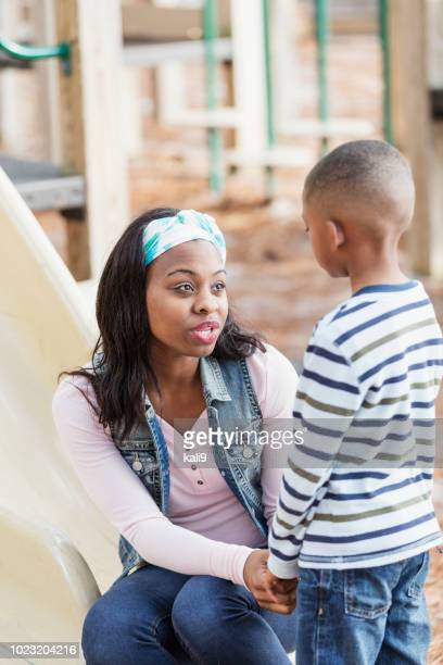mother talking to little boy on playground - obedience stock pictures, royalty-free photos & images