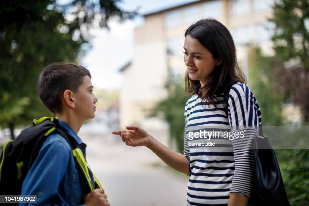 madre hablar hijo frente a la escuela - penalty fotografías e imágenes de stock