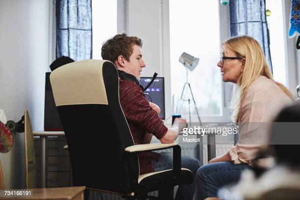 Mother talking to son sitting by computer at home