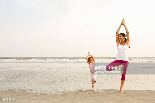 Mother teaches daughter yoga on beach