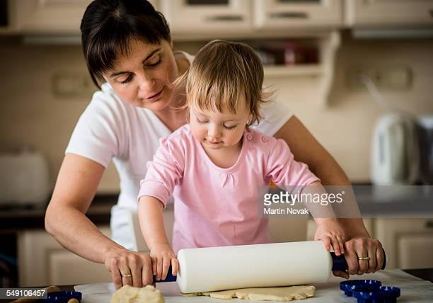 Mother teaches her child to work with rolling pin