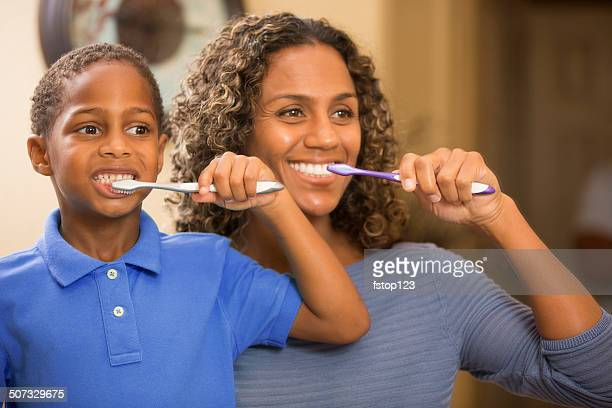 Mother teaches son how to properly brush his teeth. Bathroom.