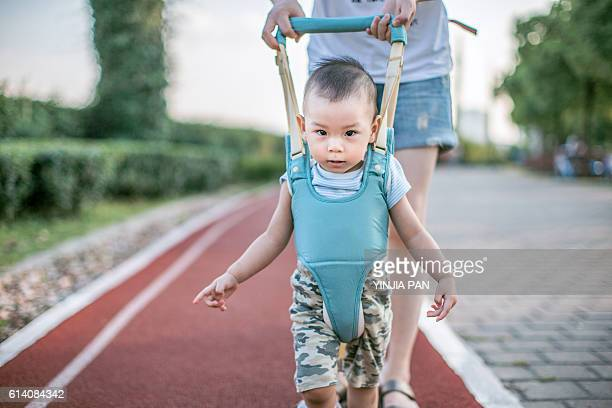 Mother teaching baby boy how to walk