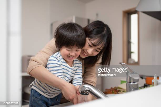 mother teaching child how to wash hands - washing hands stock pictures, royalty-free photos & images