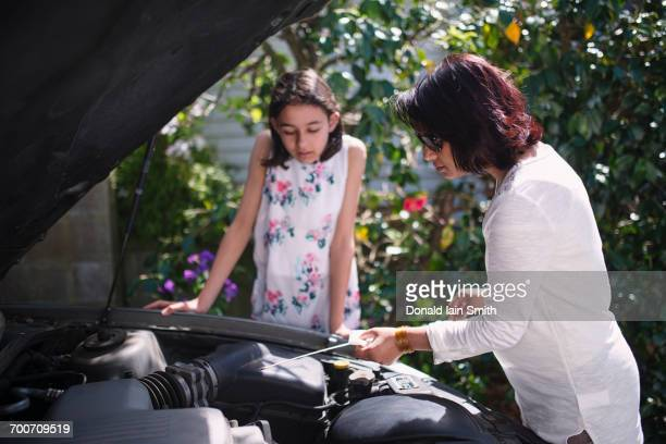Mother teaching daughter about car engine