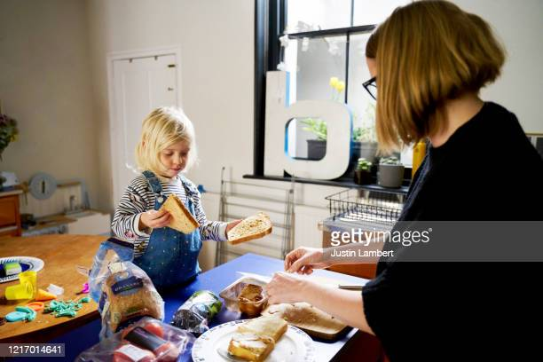 mother teaching daughter how to make lunch together in the kitchen - preparation stock pictures, royalty-free photos & images