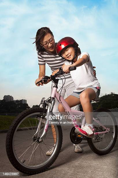 Mother teaching daughter how to ride a bicycle