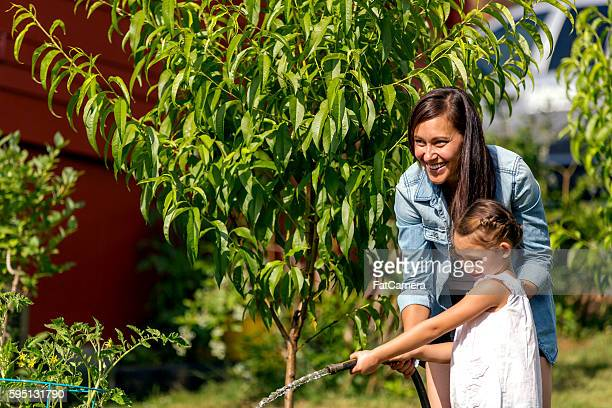 Mother teaching daughter how to water plants outdoors