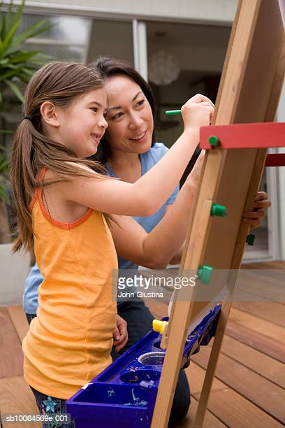 Mother teaching daughter (6-7) painting
