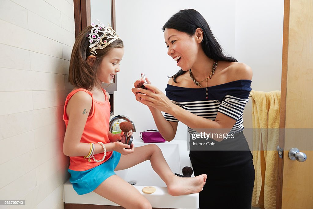 Mother teaching daughter to apply lipstick in bathroom : Foto stock