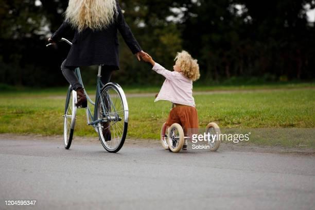 mother teaching daughter to bicycle - hulp stockfoto's en -beelden