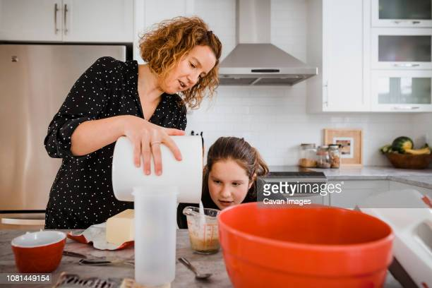 mother teaching daughter to cook in kitchen at home - cavan images foto e immagini stock