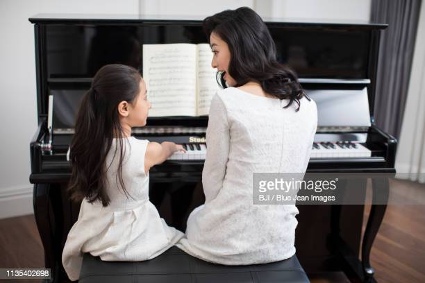 mother teaching daughter to play the piano - luxury girl stock photos and pictures