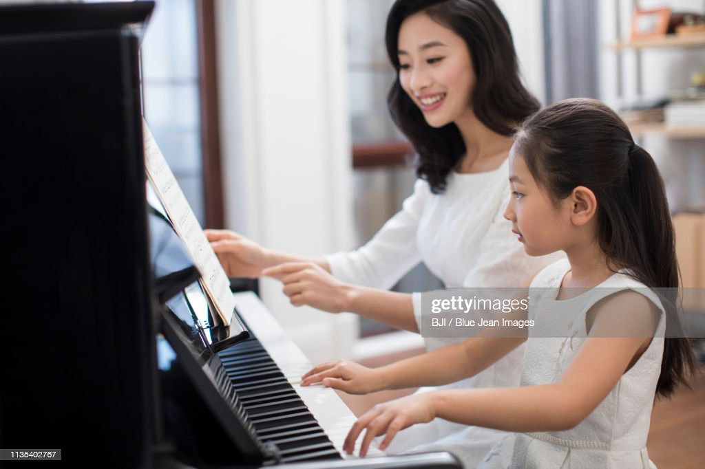 Mother teaching daughter to play the piano : ストックフォト